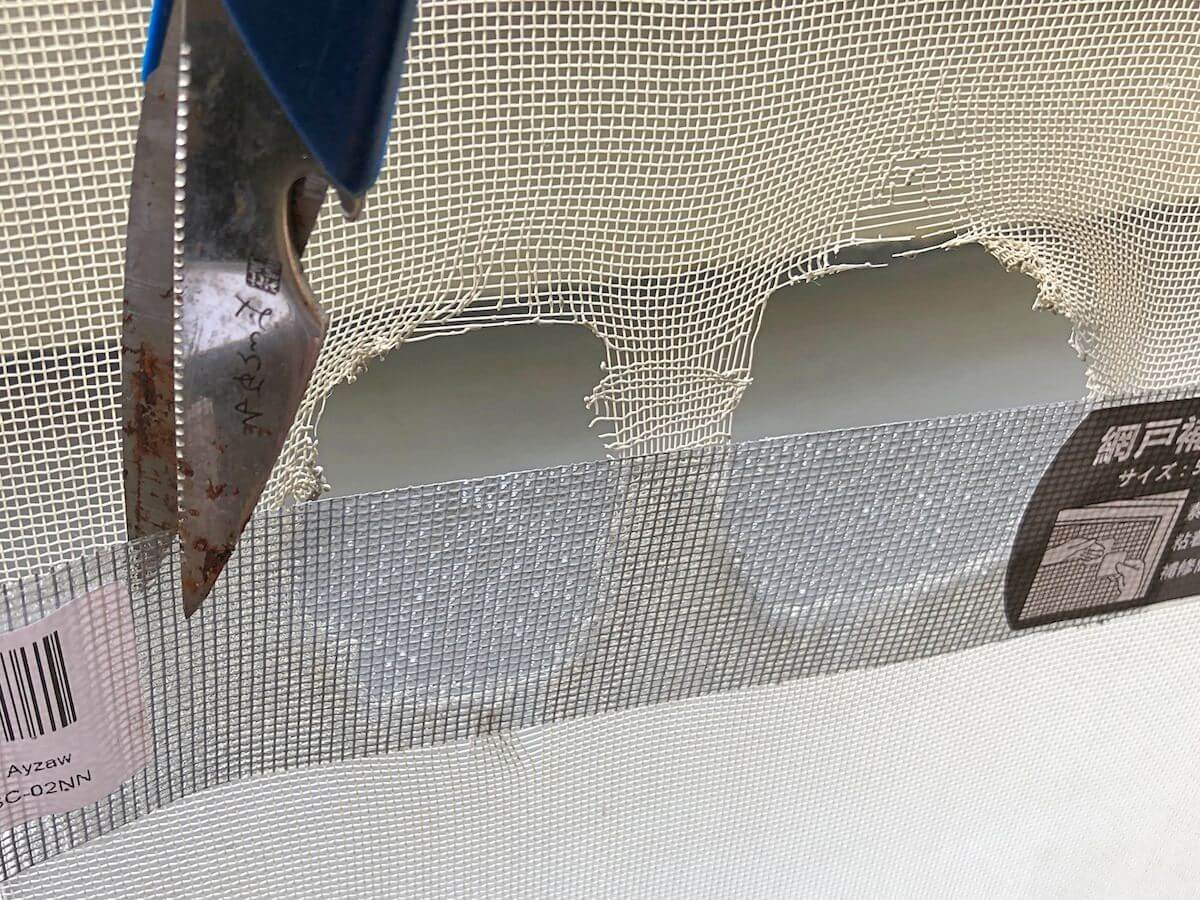 網戸補修テープをハサミで切る